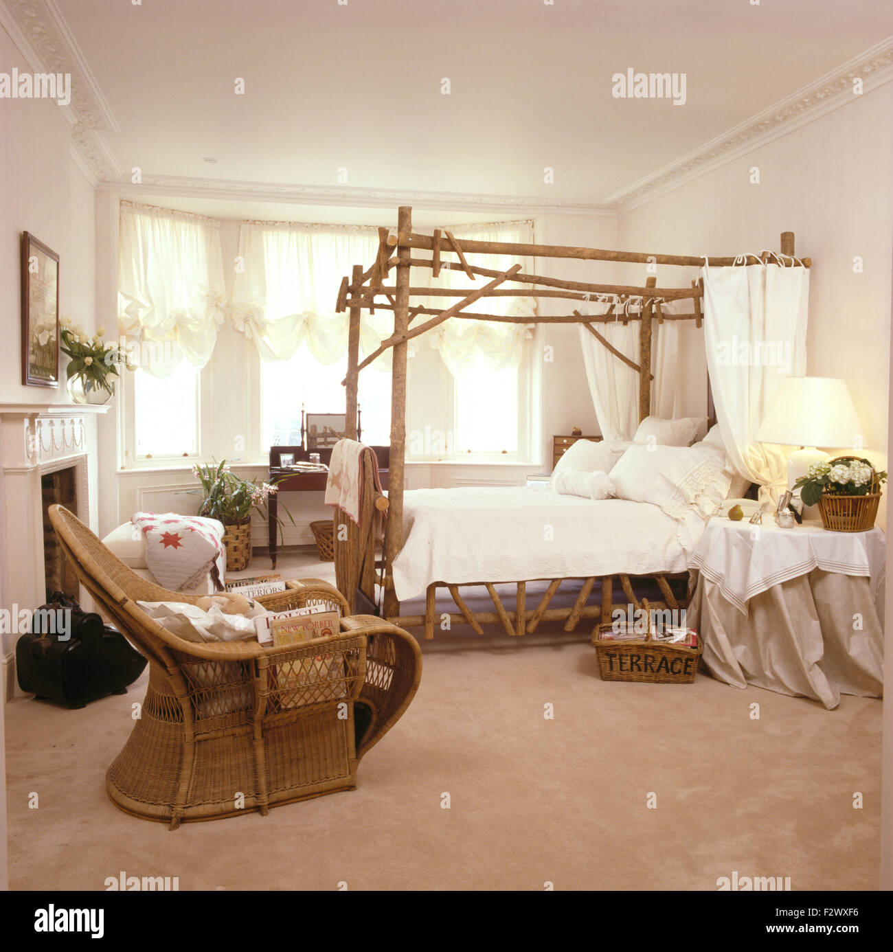 Cane Chair In Nineties Bedroom With Rustic Wooden Four Poster Bed Stock Photo Alamy