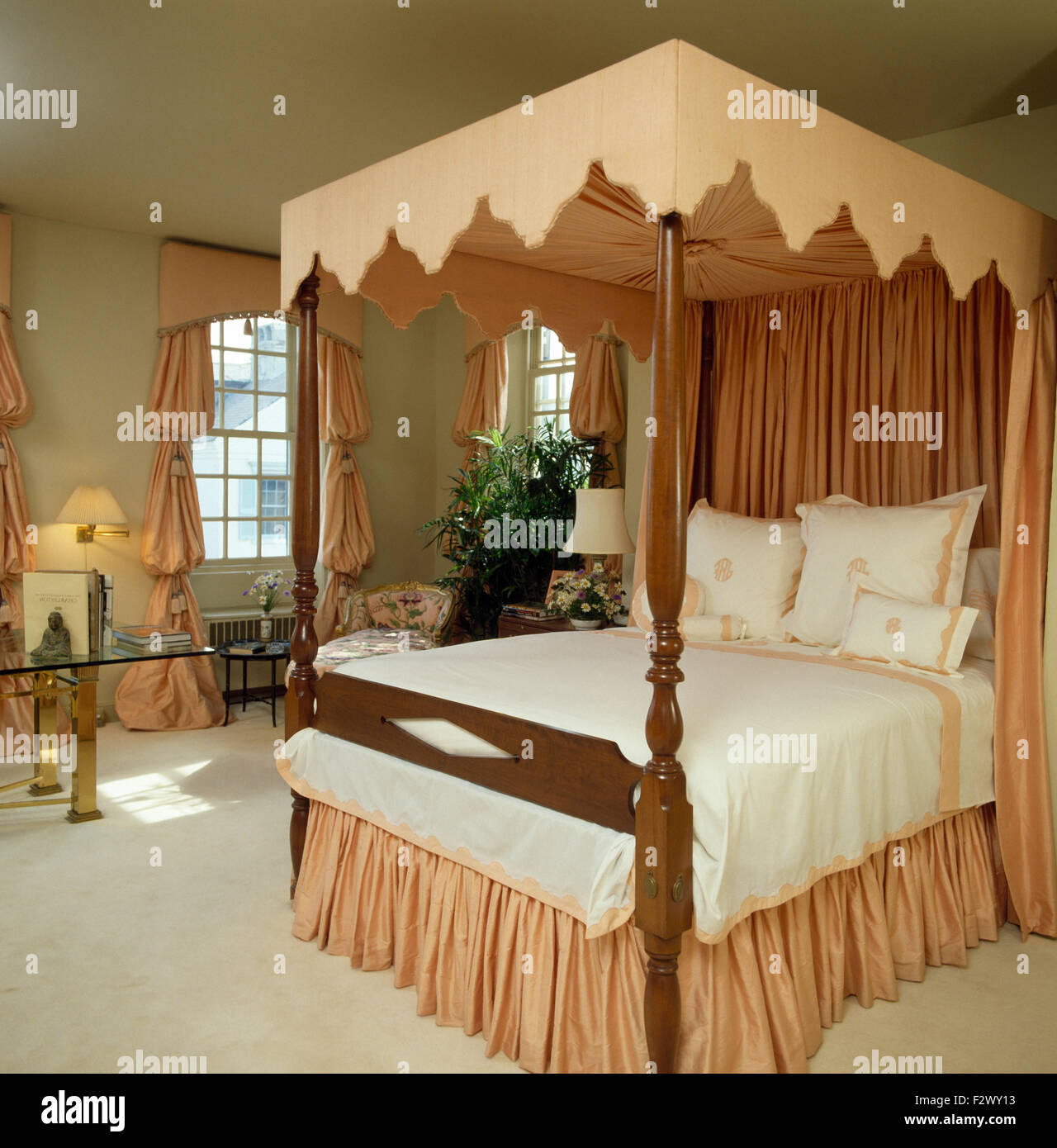 Peach pelmet and drapes on four poster bed in eighties bedroom Stock Photo