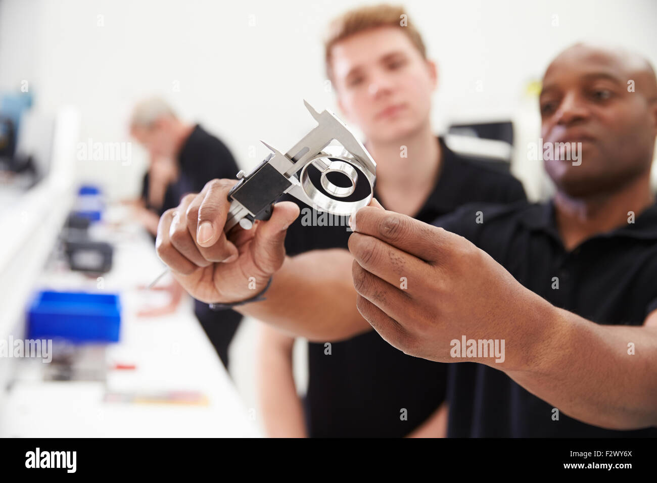 Engineer In Factory With Apprentice Checks Component Quality - Stock Image