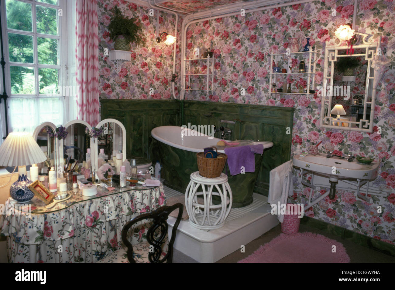 Slipper bath on small platform in corner of eighties bathroom with rose patterned wallpaper Stock Photo