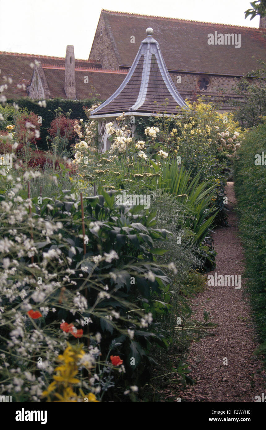 White crambe and roses in border beside gravel path to hexagonal summerhouse with a tiled roof - Stock Image