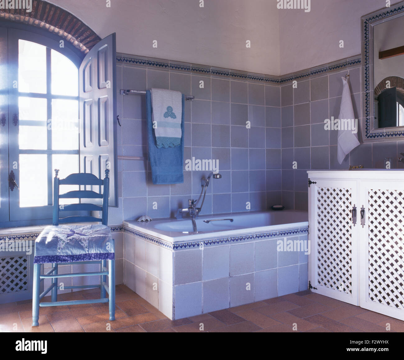 Painted Ladder Back Chair In Pale Blue Grey Tiled Spanish Bathroom Stock Photo Alamy