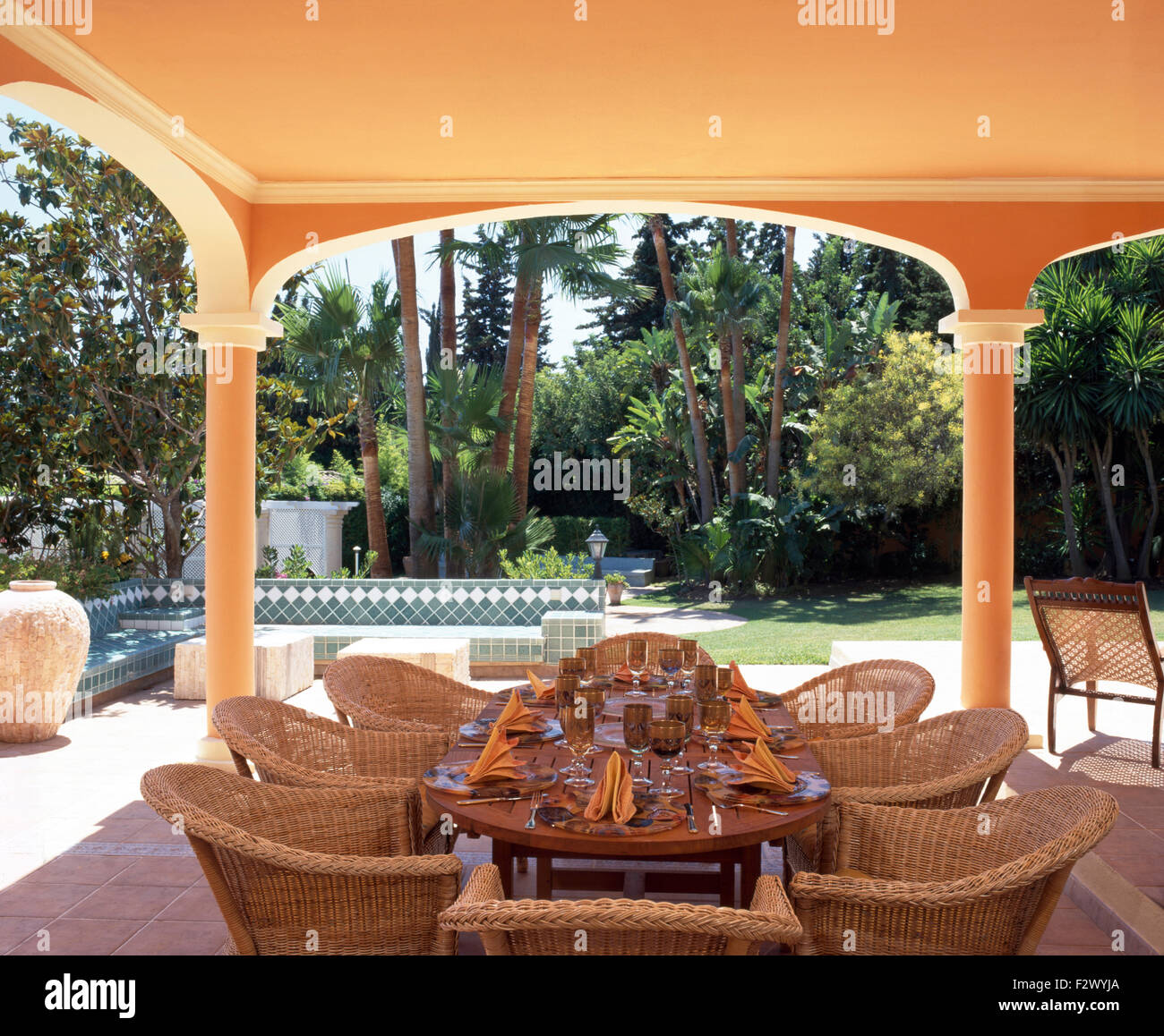 Wicker chairs at table set for lunch on veranda of Spanish villa with a view of the garden with tall trees & Wicker chairs at table set for lunch on veranda of Spanish villa ...