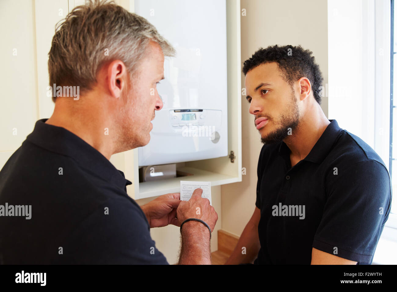 Boiler technician and apprentice servicing domestic boiler - Stock Image