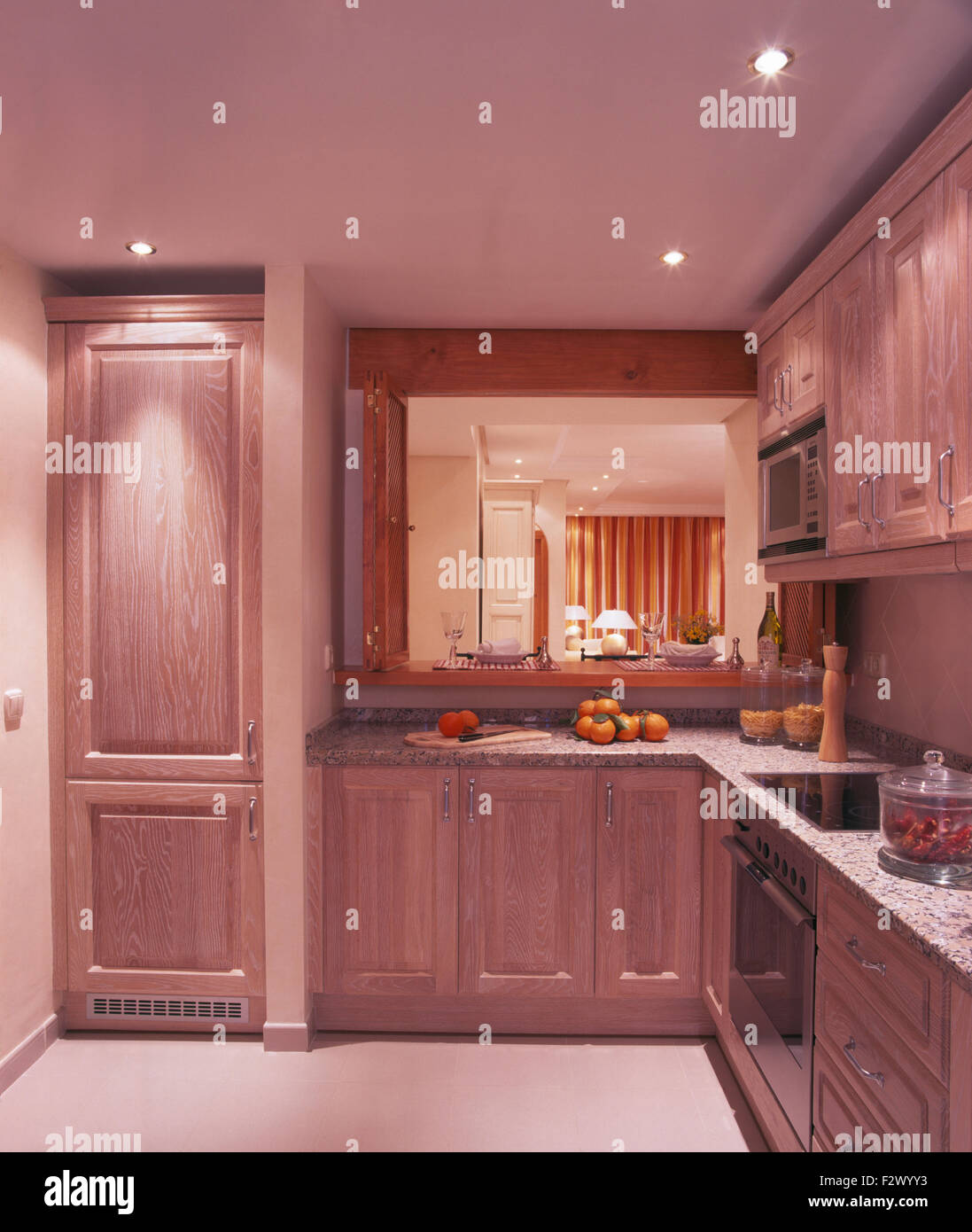 Recessed lighting in modern Spanish kitchen with a hatch and fitted cupboards with wooden doors - Stock Image