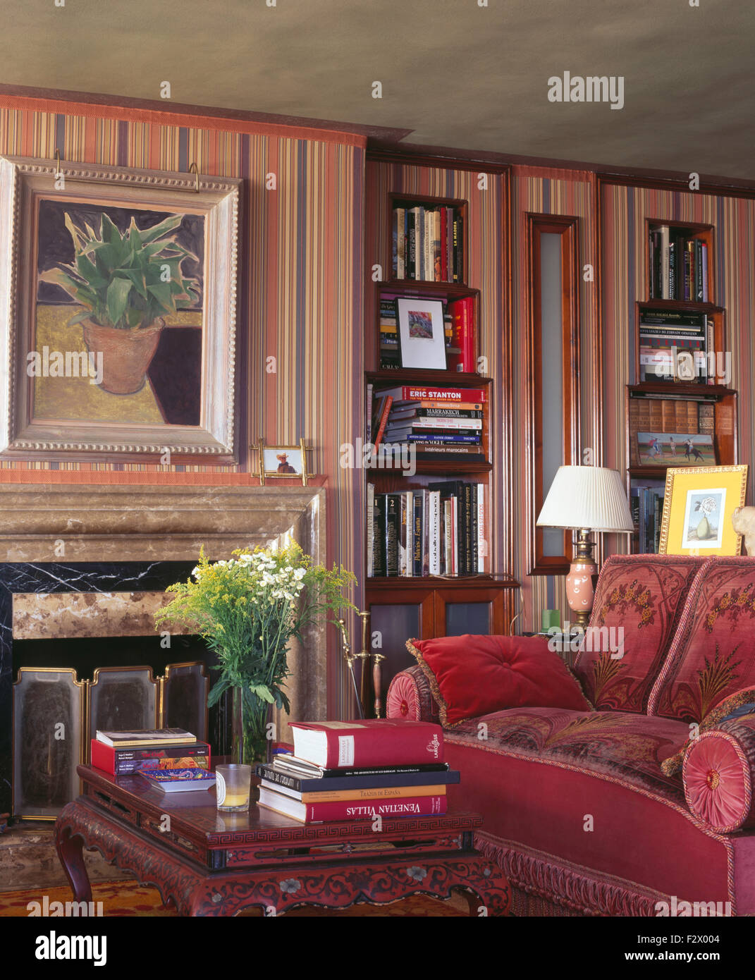 Hardback Books On Coffee Table Beside Fireplace And Red Sofa In Spanish  Living Room With Striped Wallpaper