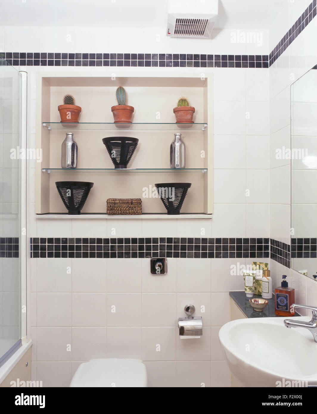 Black mosaic tiled border in modern white bathroom with glass ...