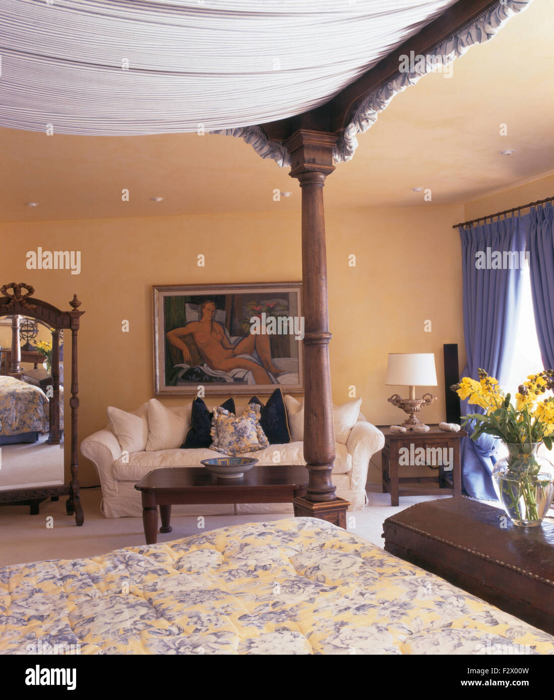 Four poster bed and cream sofa in Spanish country bedroom - Stock Image