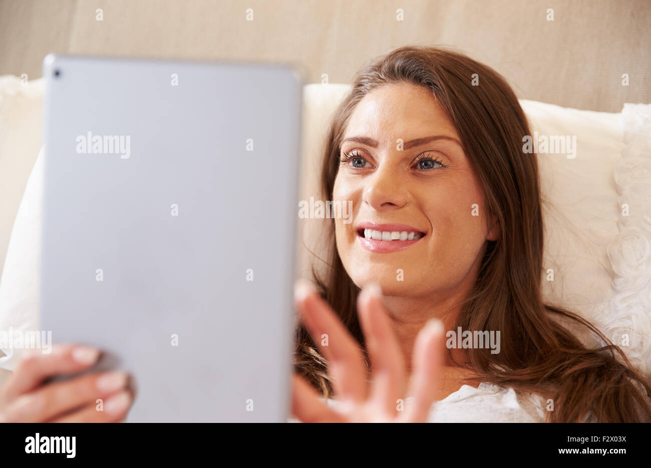 Woman Lying In Bed Whilst Using Digital Tablet - Stock Image