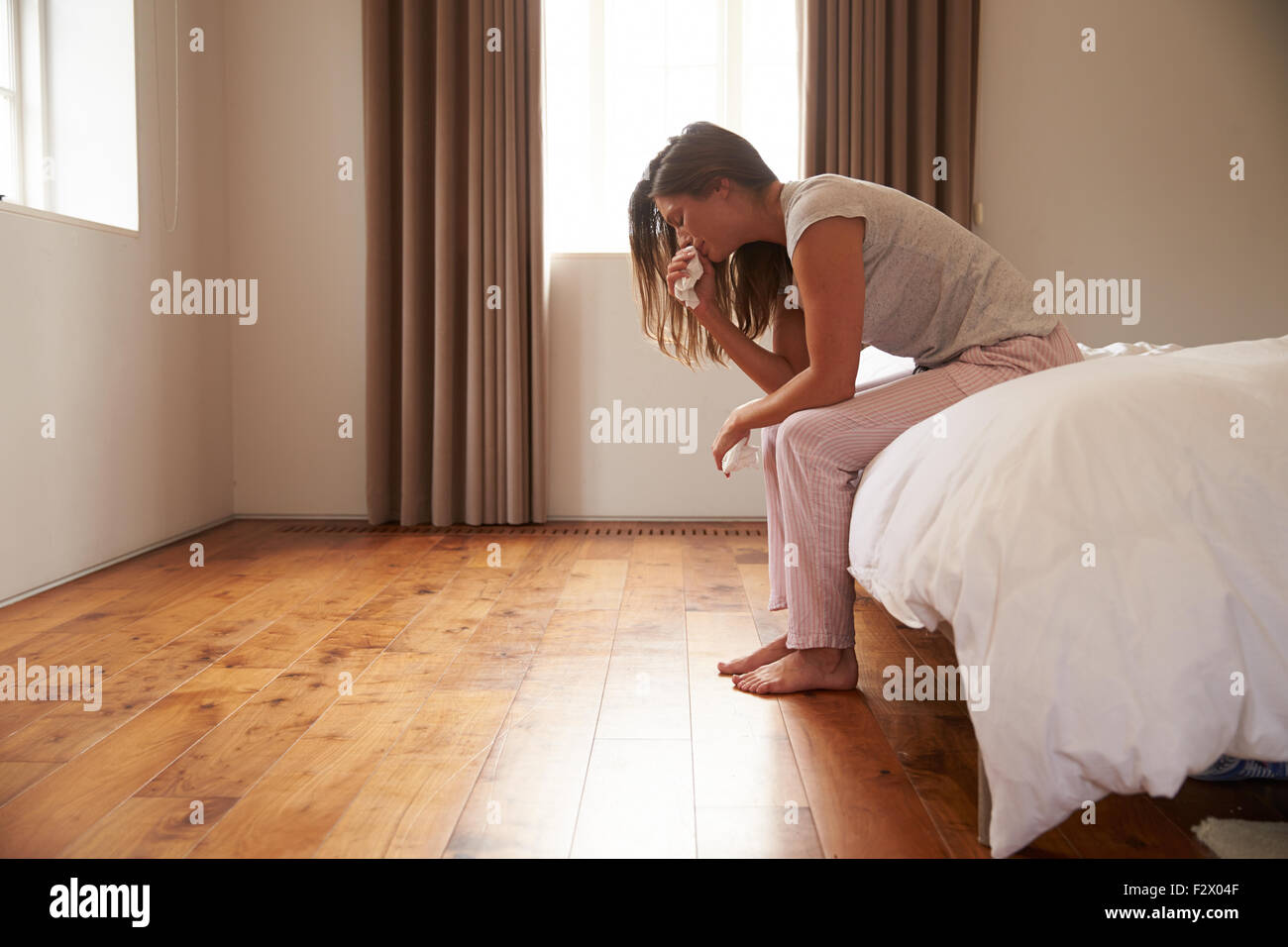 Woman Suffering From Depression Sitting On Bed And Crying - Stock Image