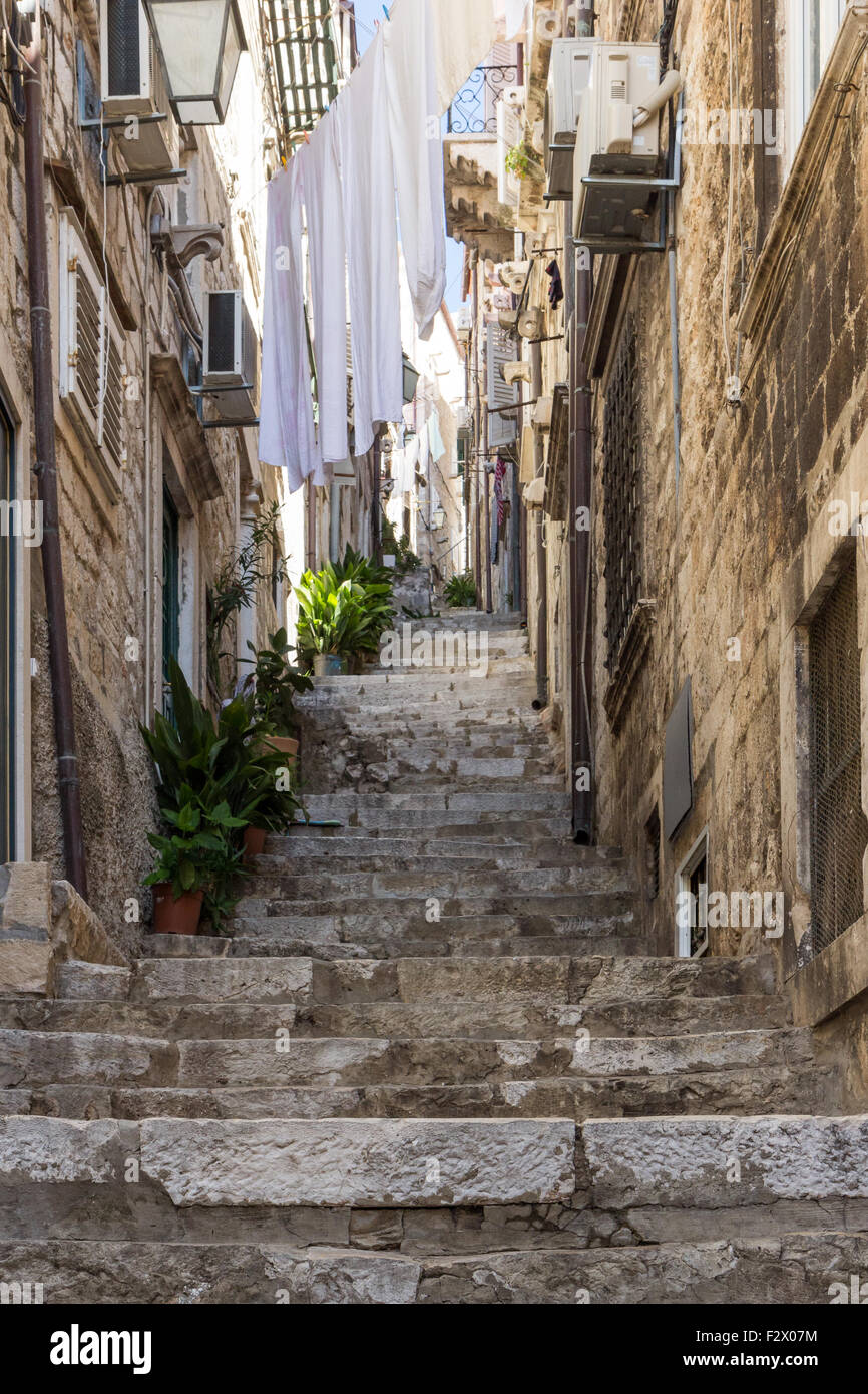 Narrow and empty alley, stairs and laundry hanging above at the Old Town in Dubrovnik, Croatia. - Stock Image