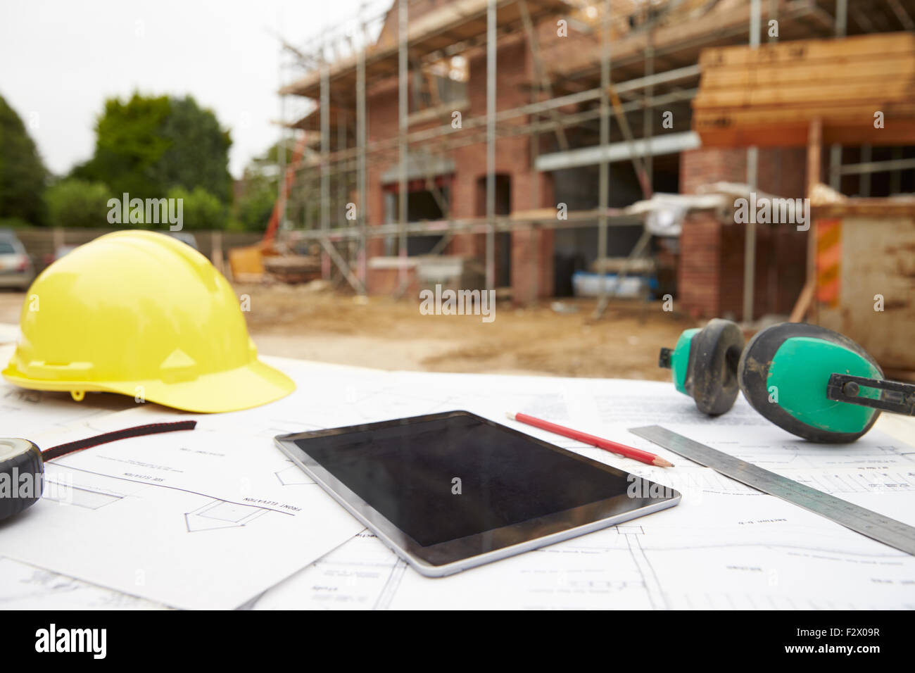 Close Up Of Plans And Digital Tablet On Building Site - Stock Image