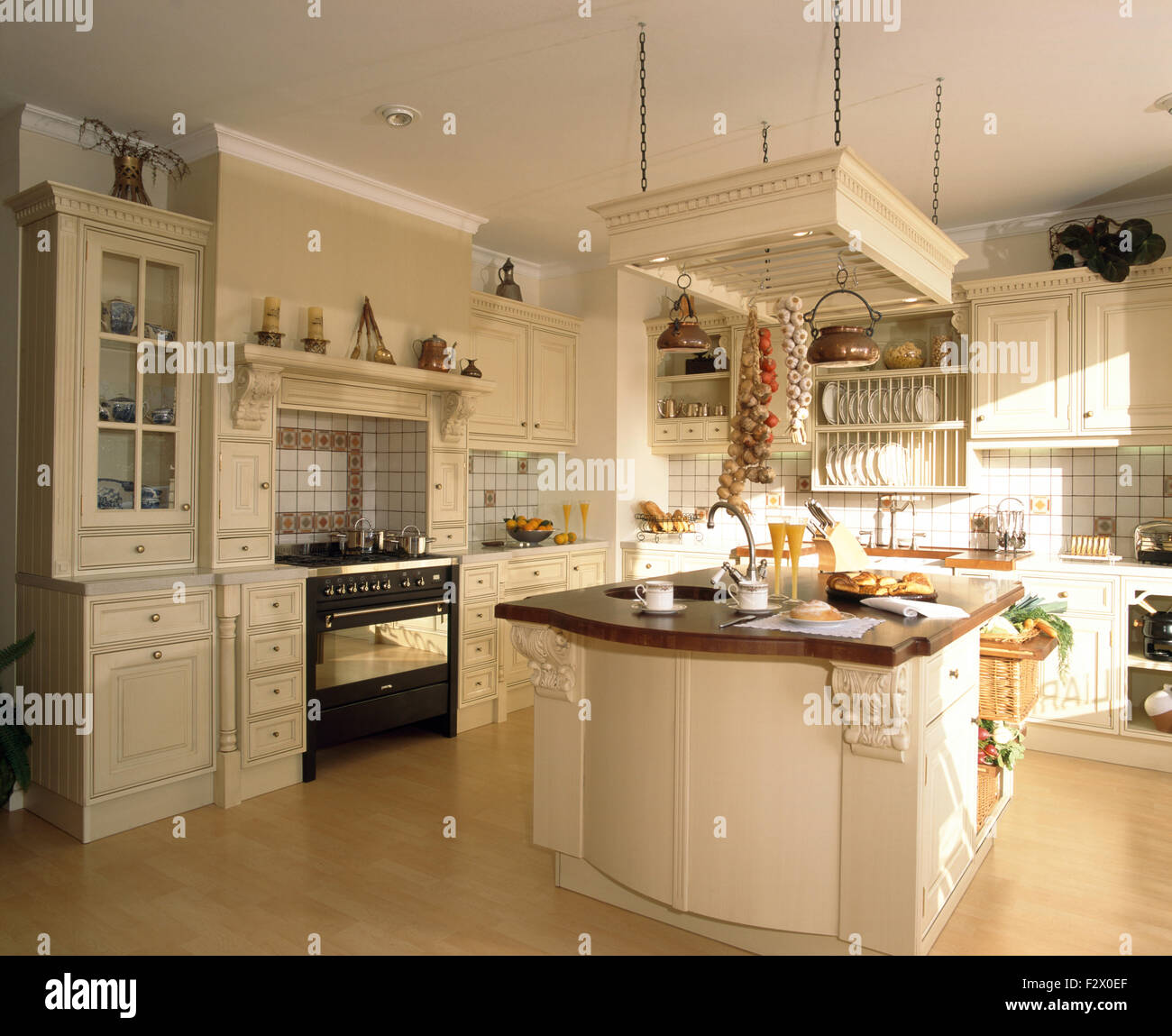 Sink in island unit in modern Spanish kitchen with a range oven ...