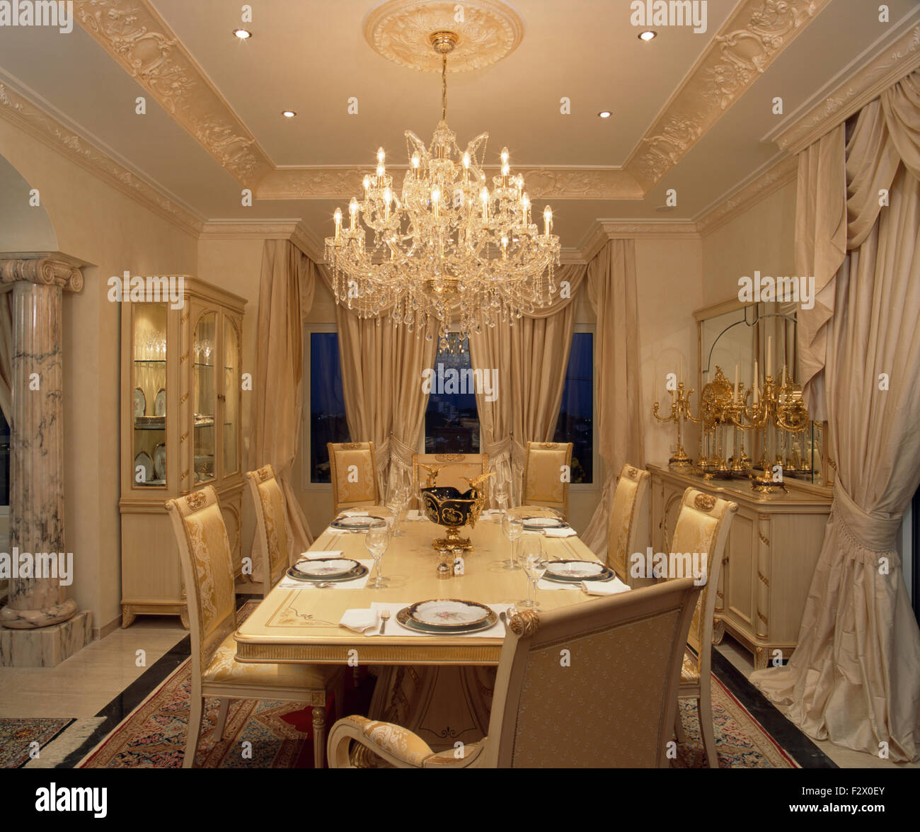 ornate glass chandelier above table set for dinner in opulent spanish dining room with cream silk drapes