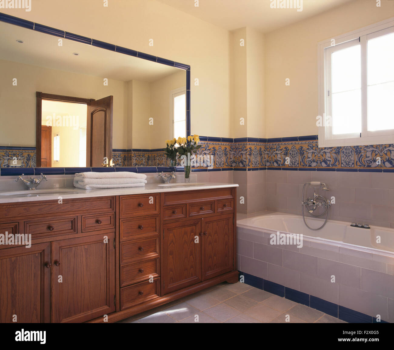 Large Mirror Above Wooden Vanity Unit In Modern Spanish Bathroom With A  Tiled Border Above The Bath