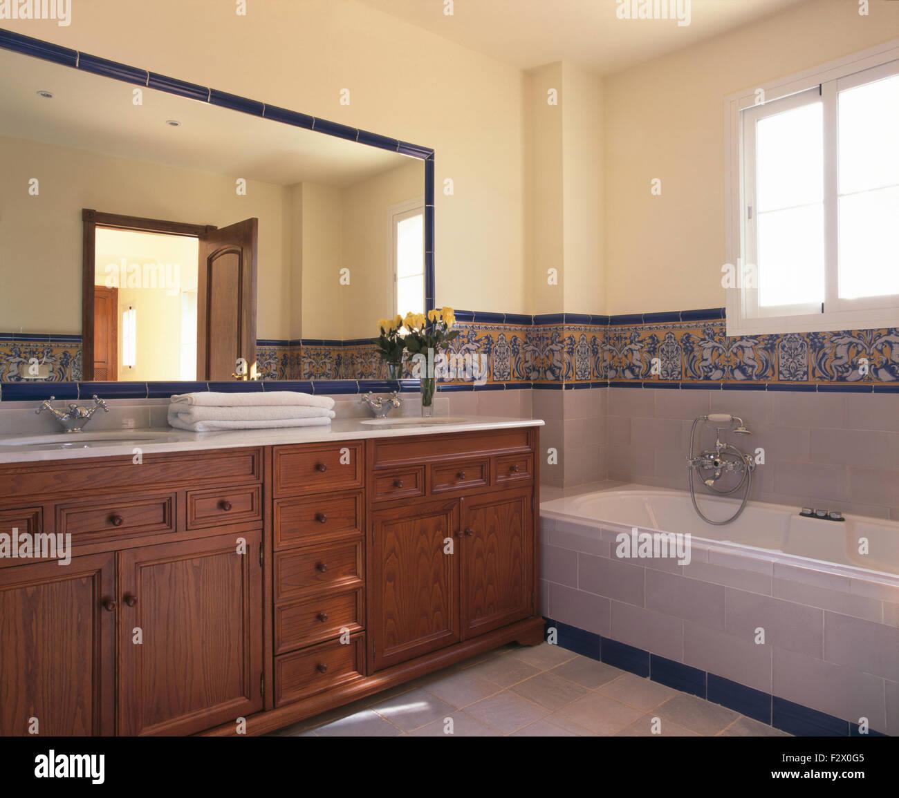 Large mirror above wooden vanity unit in modern Spanish bathroom ...