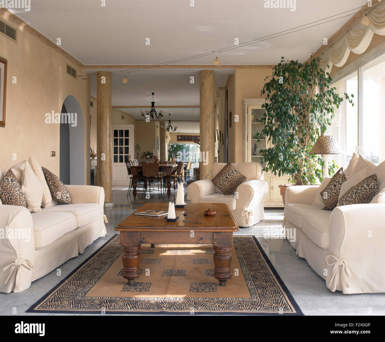 Cream Loose Covers On Sofas Either Side Of Rustic Wooden Coffee Table In  Open Plan Spanish Living Room