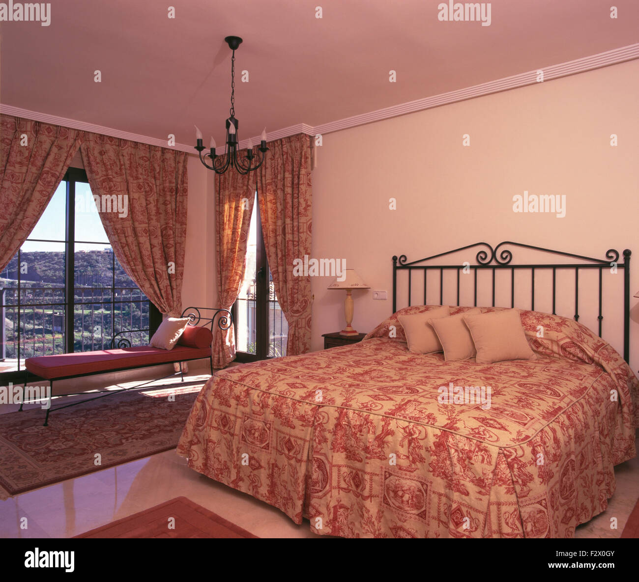 Pink patterned quilt on metal bed in Spanish bedroom with co-ordinating curtains on glass doors to balcony - Stock Image