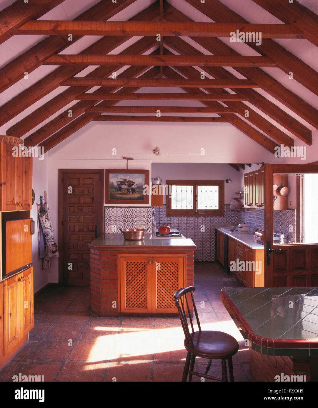 Wooden Beams On Apex Ceiling In Spanish Country Kitchen With Fretwork Doors  On Island Unit