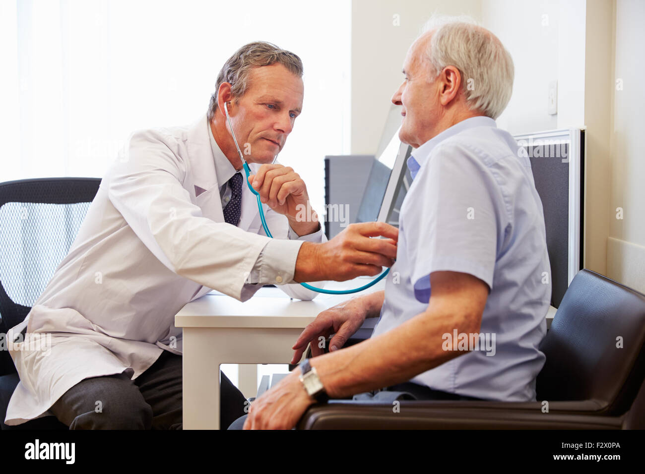 Senior Patient Having Medical Exam With Doctor In Office - Stock Image