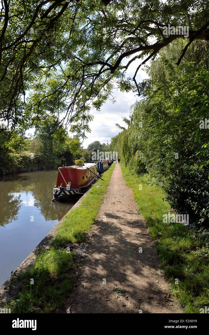 View along towpath on the Grand Union Canal at Rickmansworth, England. A line of narrow boats are tied up at their - Stock Image