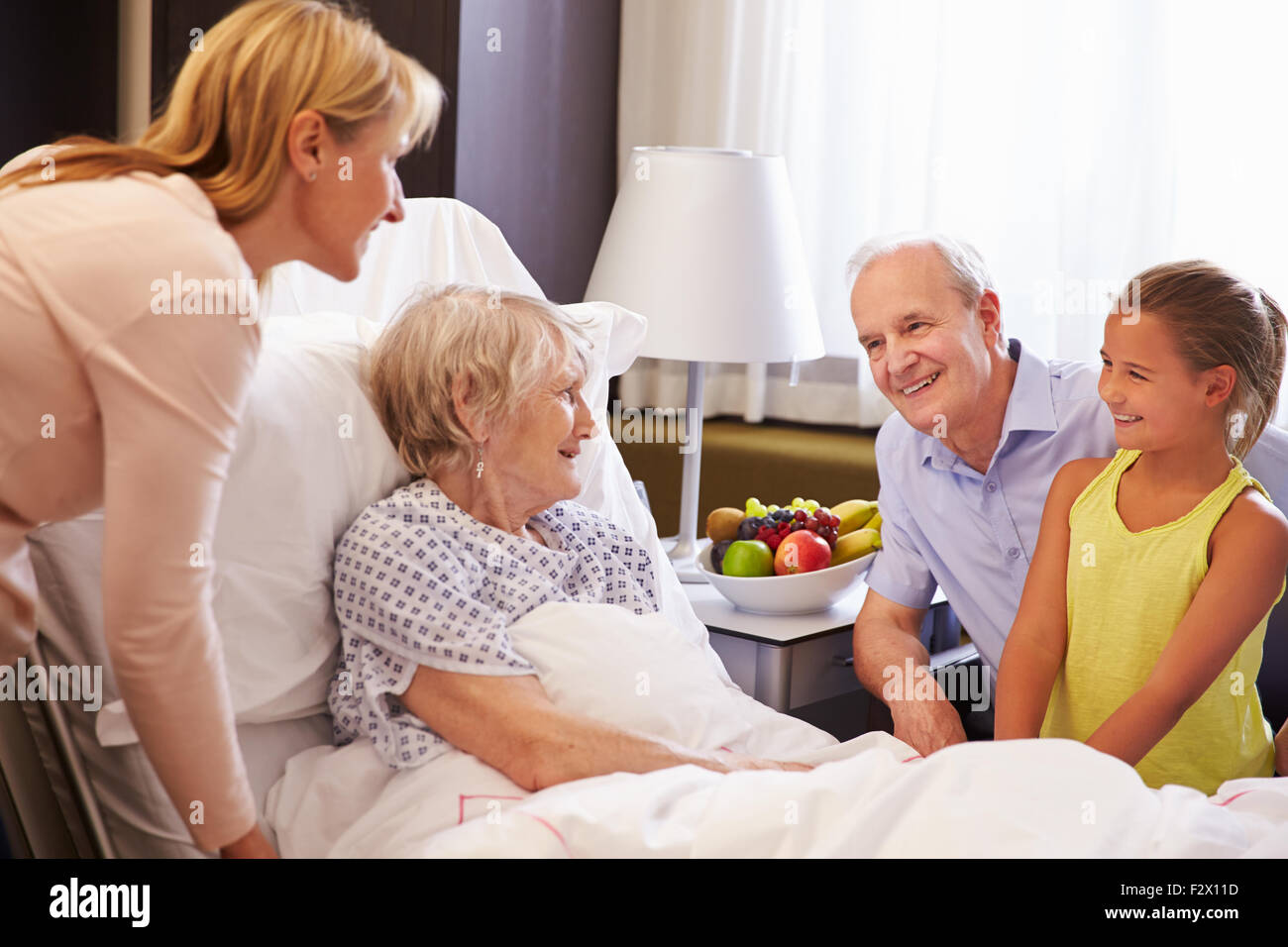 Family Visit To Grandmother In Hospital Bed - Stock Image