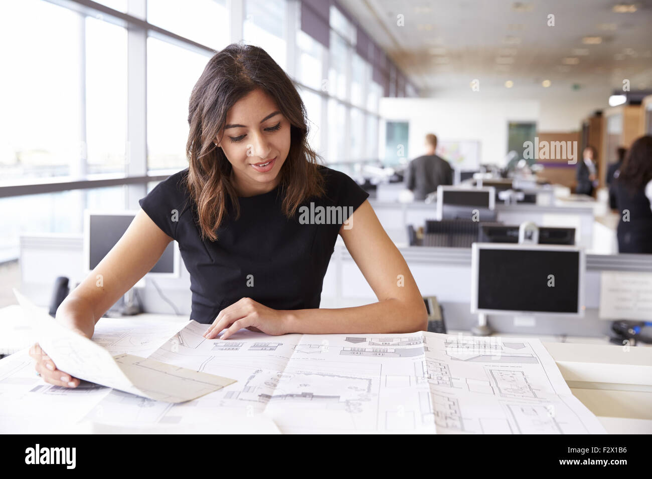 Young female architect working with blueprints in an office - Stock Image