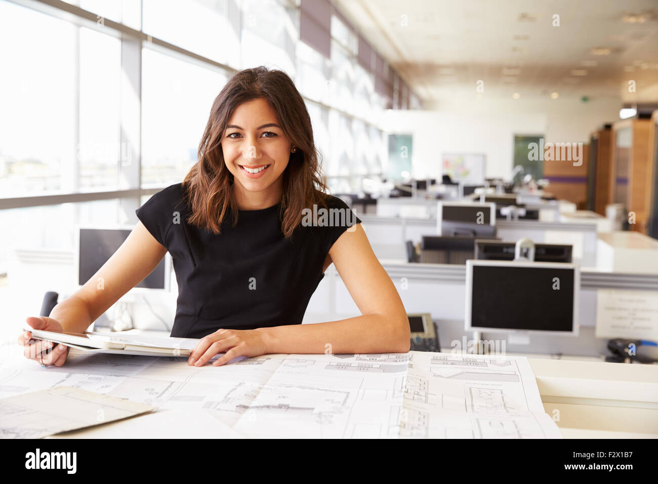 Young female architect working with computer and blueprints - Stock Image