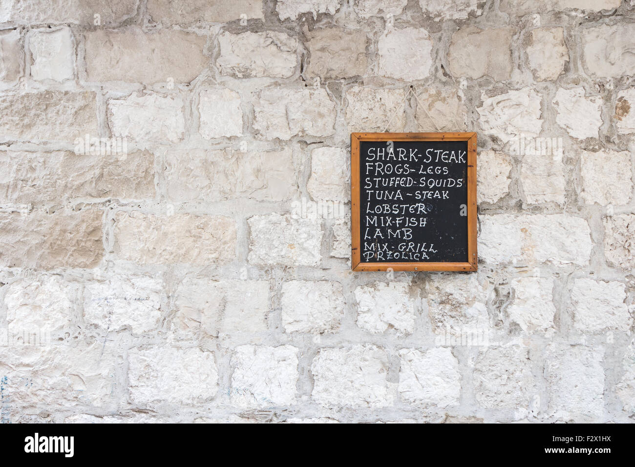 Restaurant's chalk board with list of dishes on a stone wall. - Stock Image