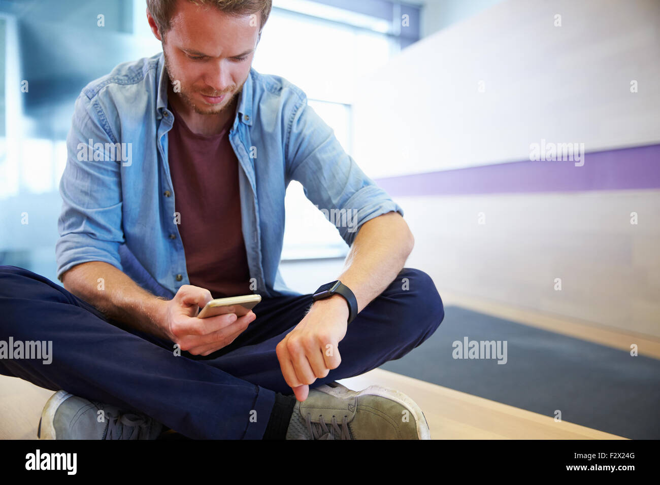 Casually dressed man with smart phone, looking at his watch - Stock Image