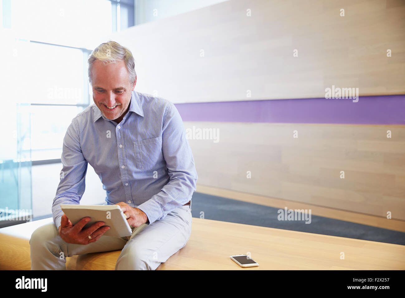 Smart casual senior man using tablet computer - Stock Image