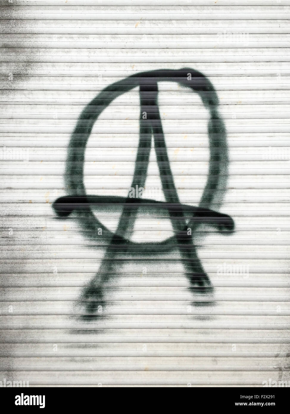 Anarchist symbol spray-painted on a shutter in Berlin, Germany. - Stock Image