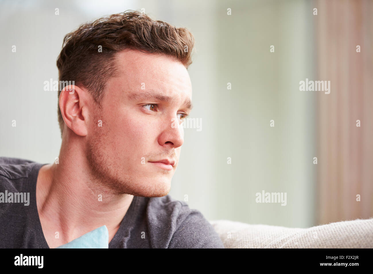 Young Man Suffering From Depression At Home - Stock Image