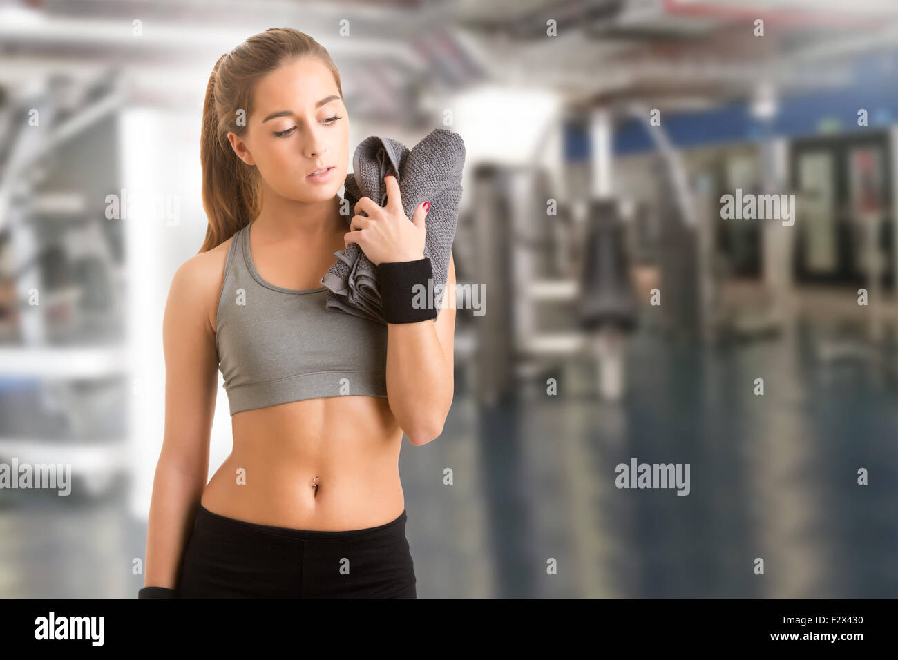 Woman resting with a towel around her neck after a fitness workout in a gym - Stock Image