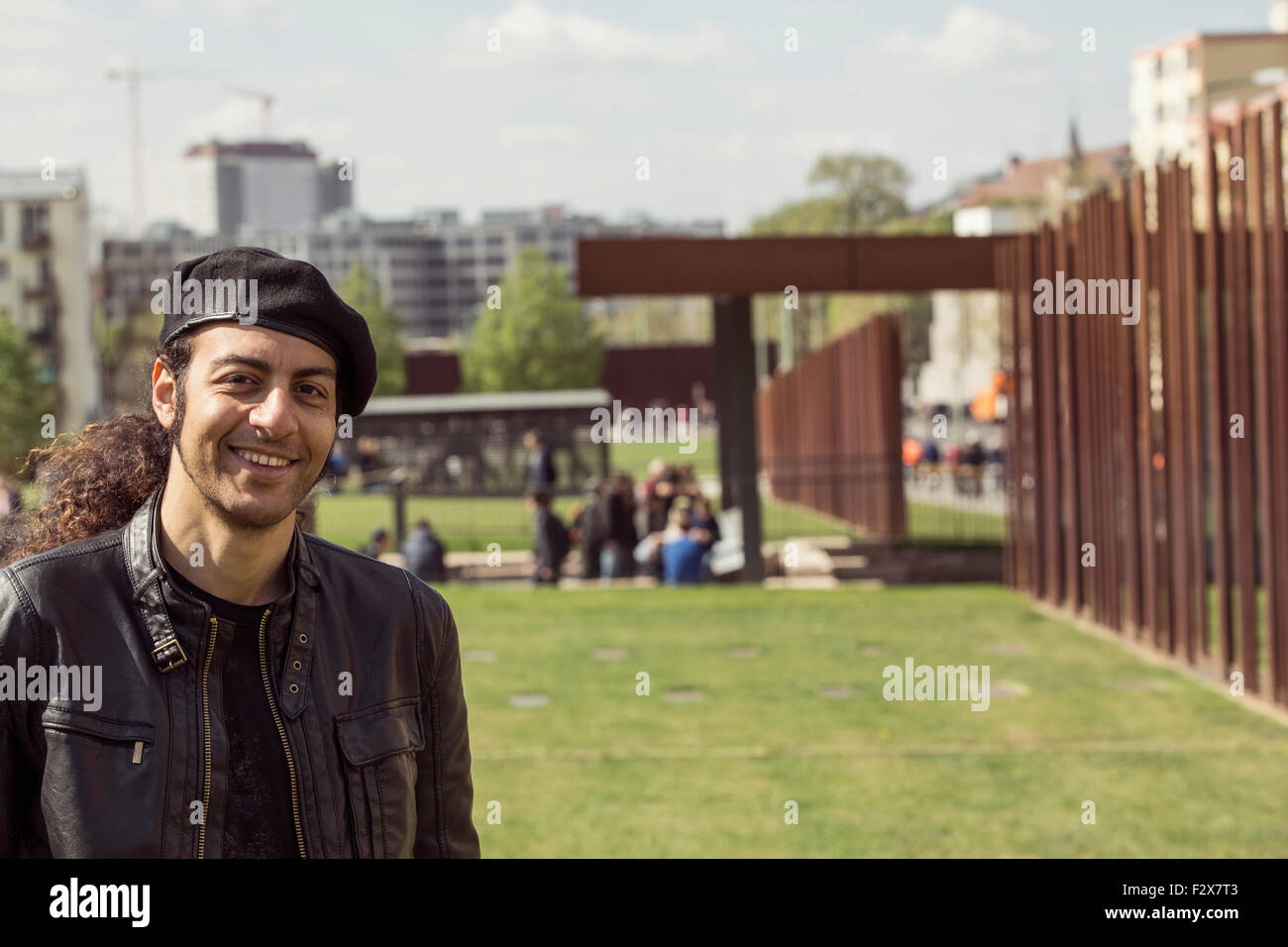 Portrait of smiling long-haired man  wearing beret and leather jacket - Stock Image