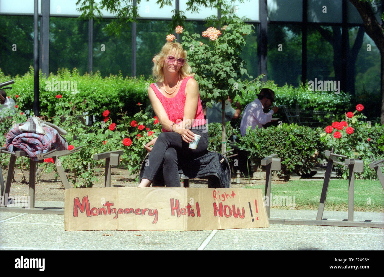 woman sitting next to sign reading, Montgomery Hotel Now!  San Jose homeless, low income residents, and activists, - Stock Image