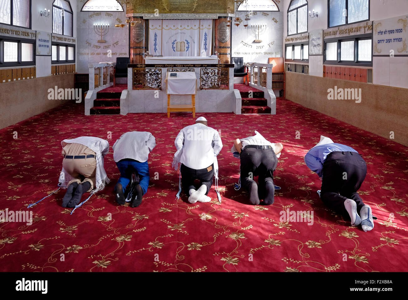 Karaite Jews bowing on the knees and prostrate during prayer in a Karaite synagogue in the city of Ramle or Ramleh Stock Photo