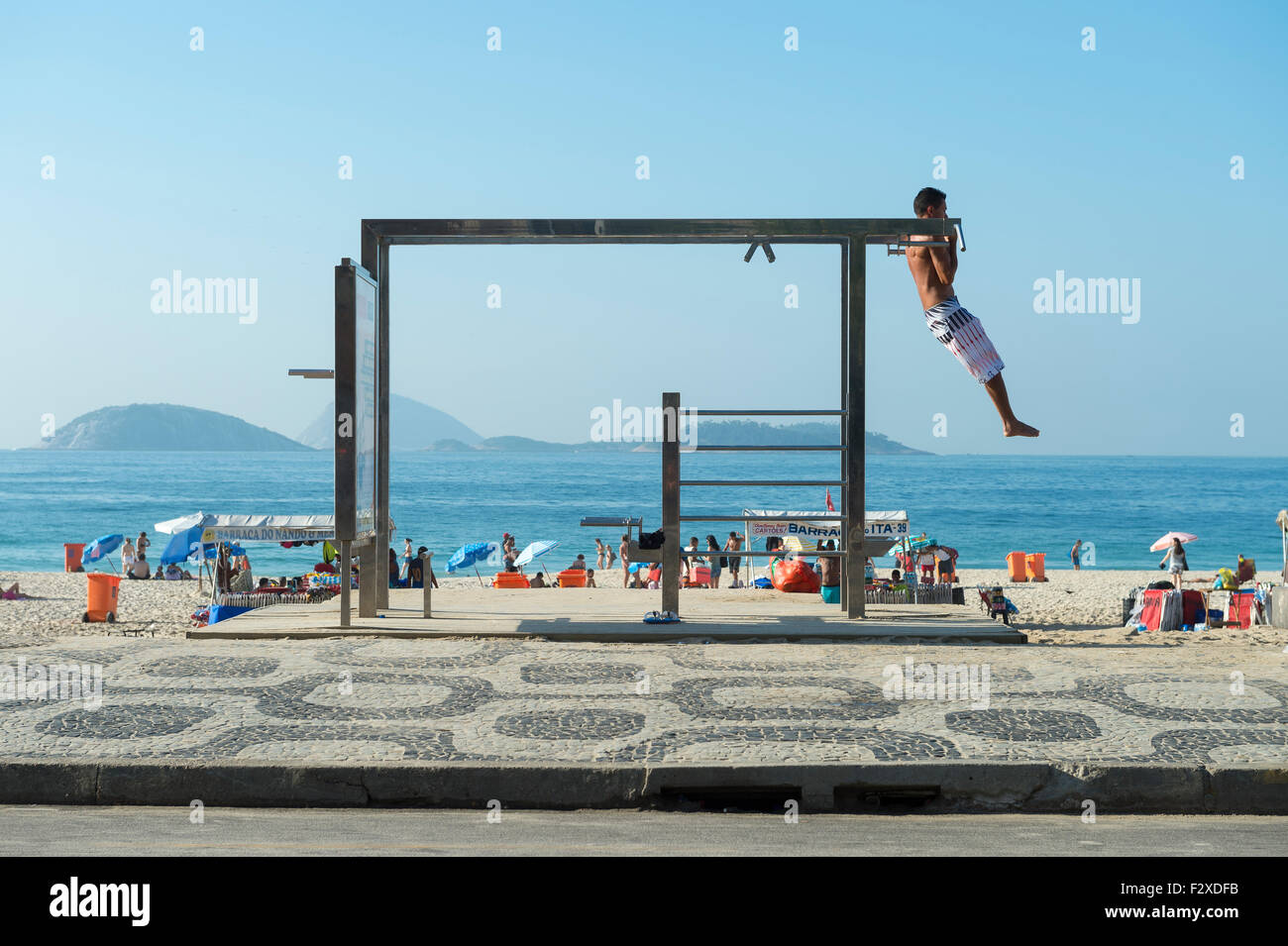 RIO DE JANEIRO, BRAZIL - FEBRUARY 22, 2015: Young man utilizes one of the many outdoor fitness stations on Ipanema - Stock Image