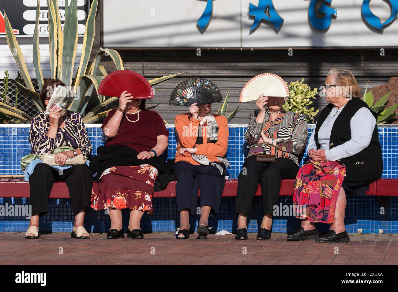 Women protecting their faces from the sun with fans, Las Palmas, Gran Canaria, Canary Islands, Spain - Stock Image