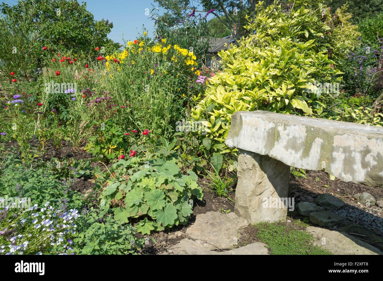 Stone seat and garden border - Stock Image