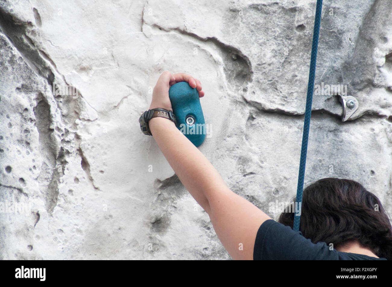 Young teen girl climbs up an artificial climbing wall Model release available - Stock Image