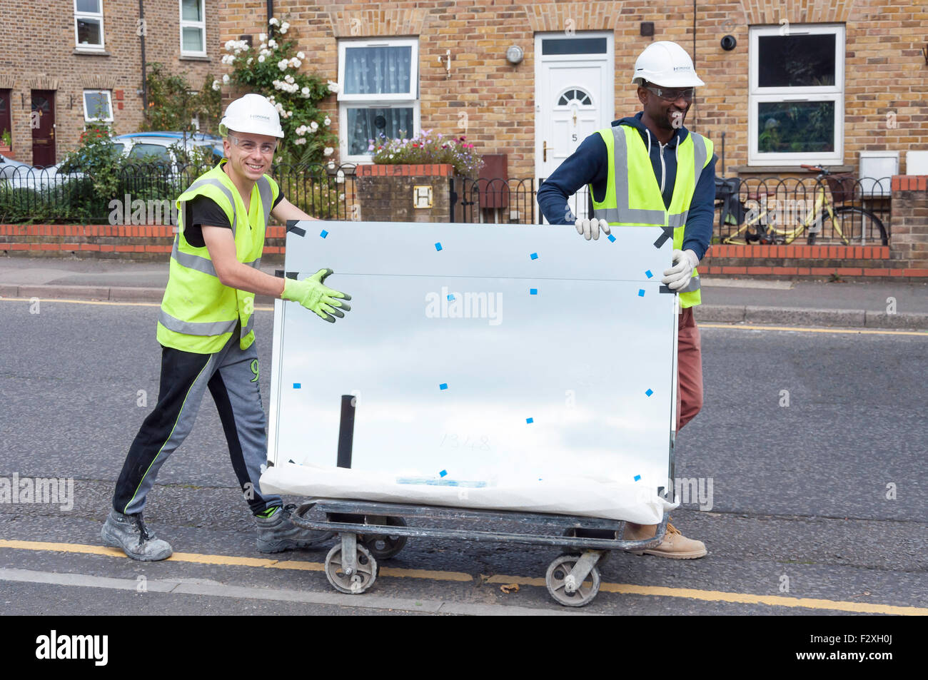 Construction workers transporting sheet of glass, Green Dragon Lane, Brentford, Greater London, England, United - Stock Image