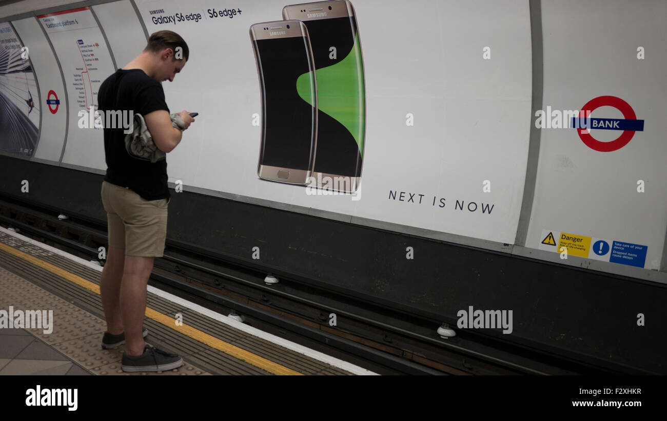 Male looking at mobile phone in front of advertising hoarding poster on London underground displaying  Samsung Galaxy Stock Photo