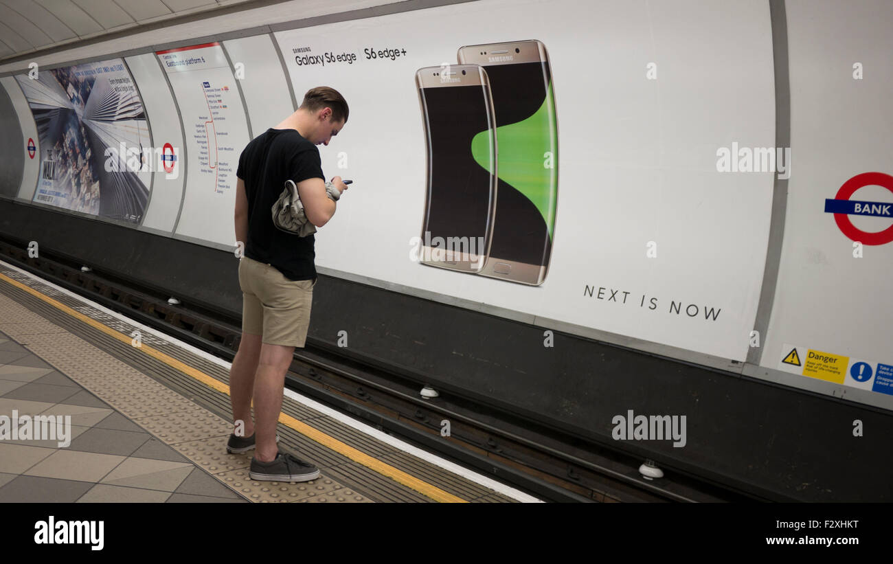 Male looking at mobile phone in front of advertising hoarding poster on London underground displaying  Samsung Galaxy - Stock Image