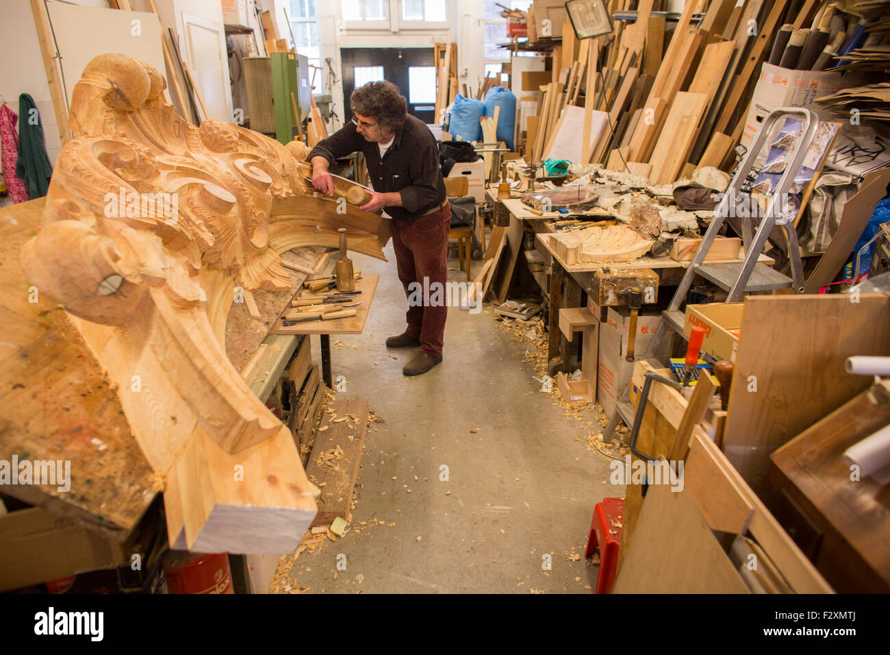Woodworker making a new house front for a Dutch canal house in Amsterdam - Stock Image