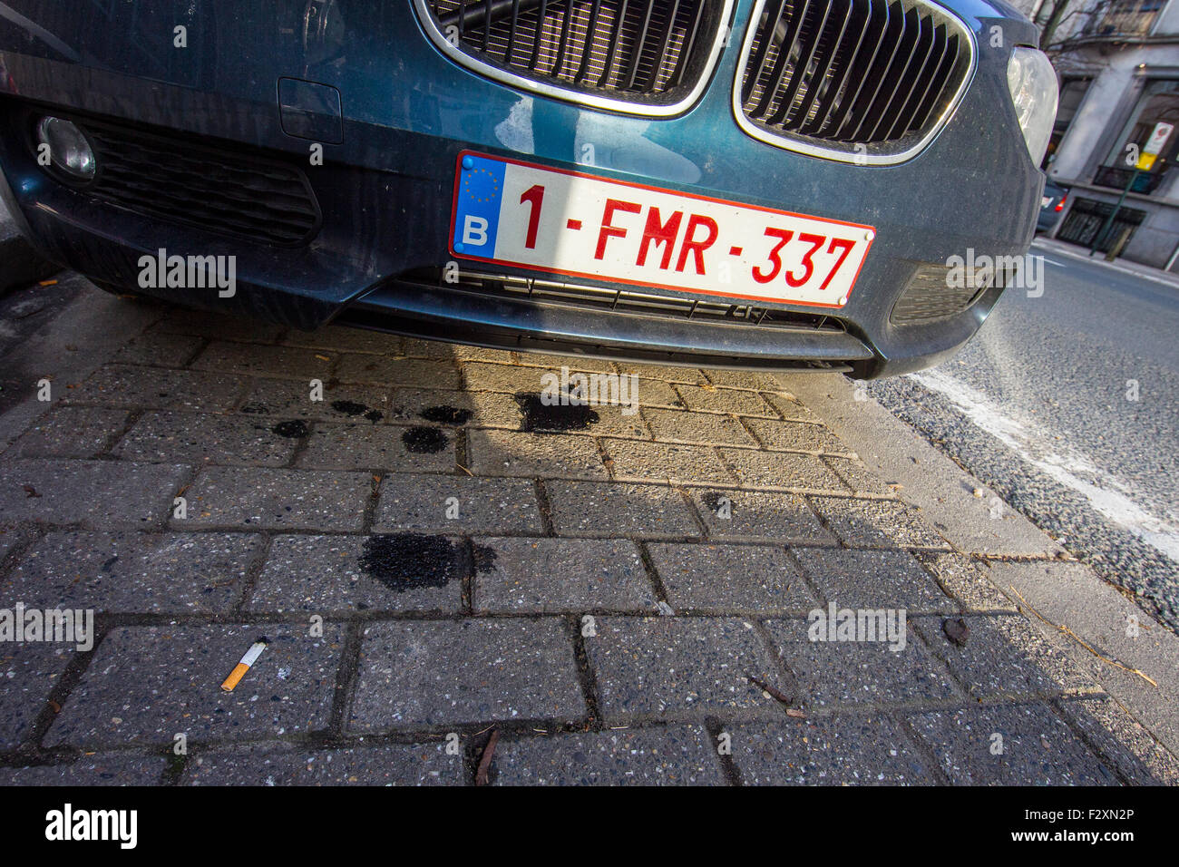oil leak drip car vehicle street pavement sidewalk - Stock Image