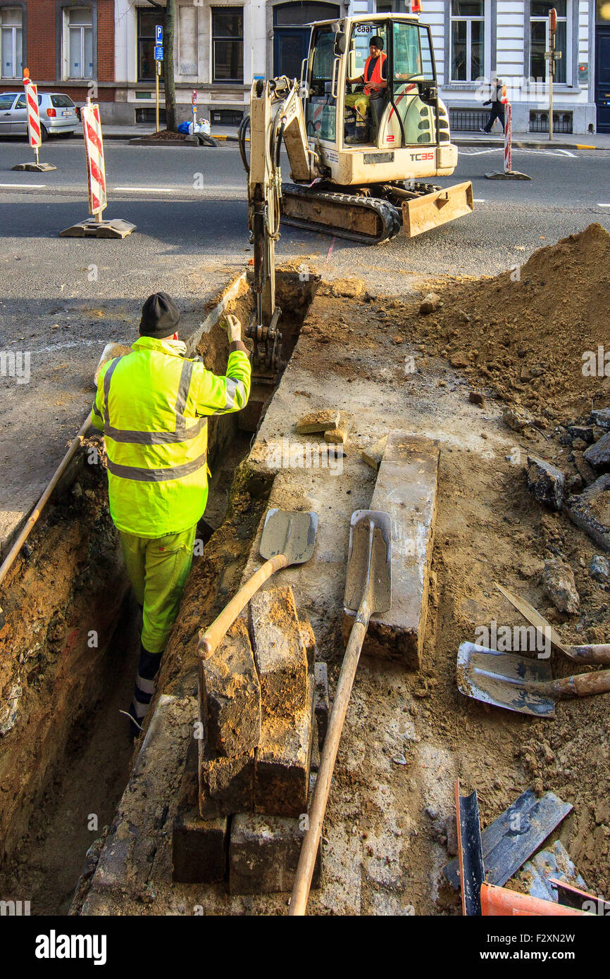 construction workers digging excavating trench machine - Stock Image