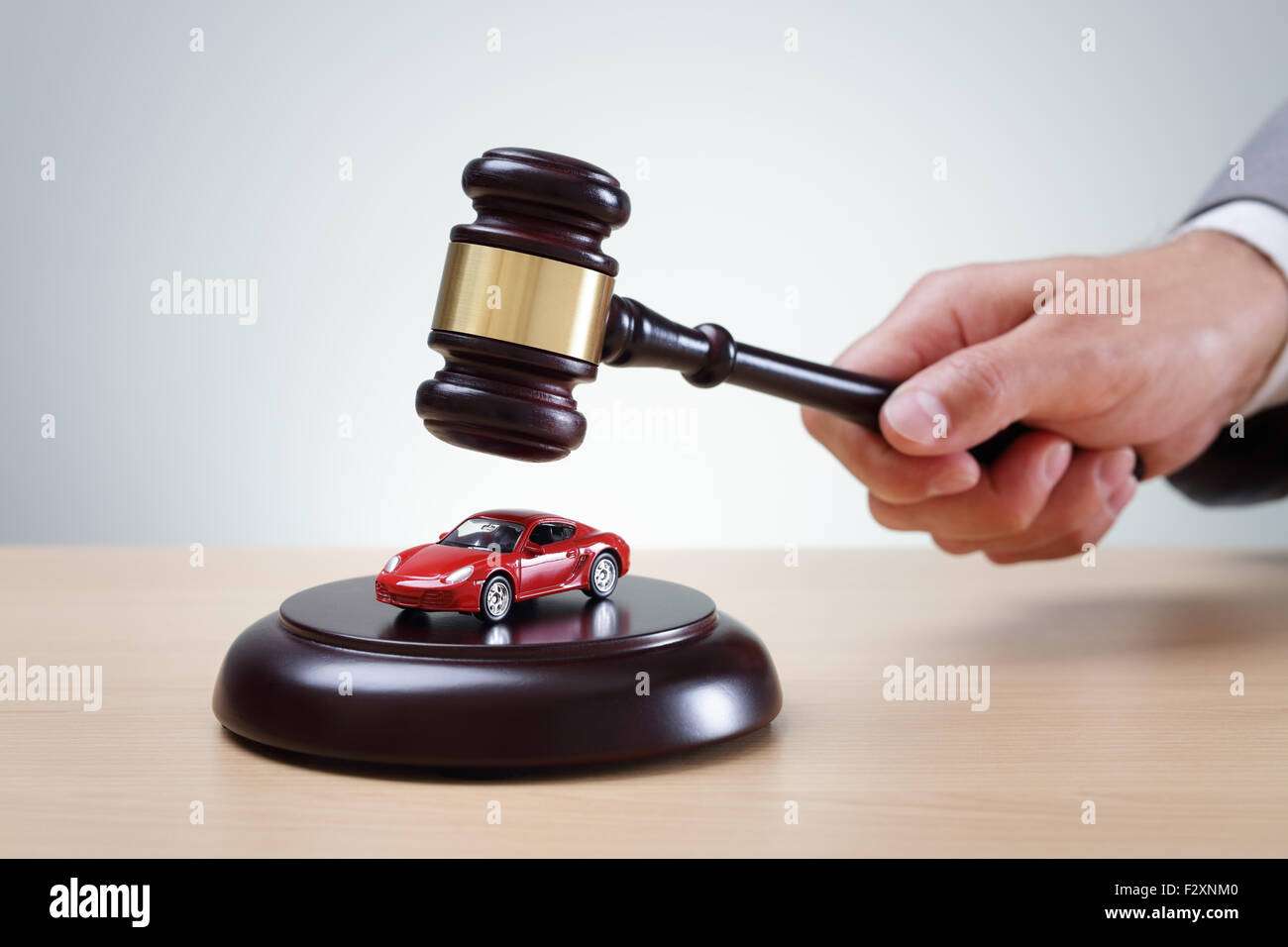 Wooden gavel and red car concept for buying and selling at auction, speeding conviction, court appearance and prosecution Stock Photo
