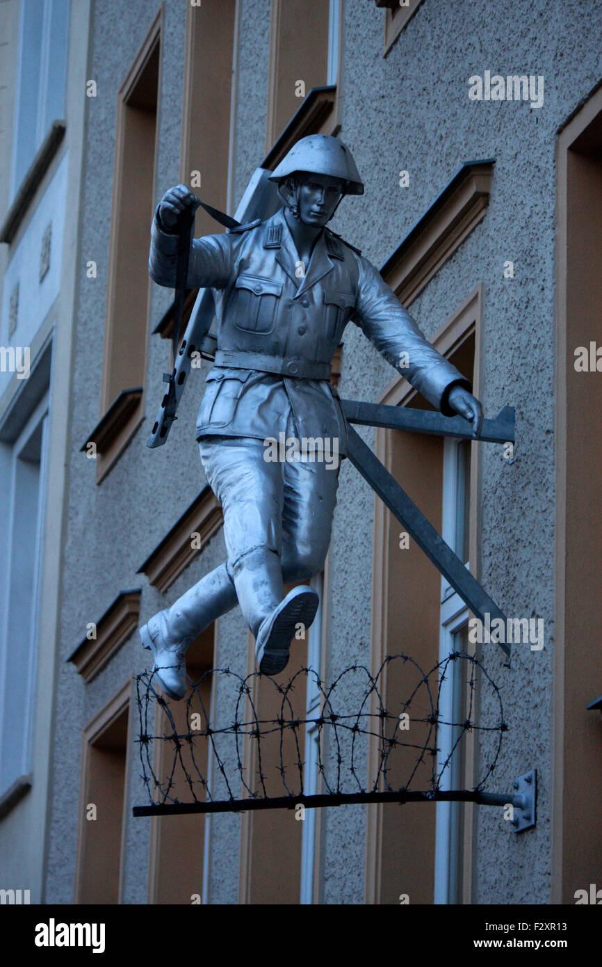 eine Skulptur, die einem beruehmten Foto eines fluechtenden NVA-Soldaten waehrend des Mauerbaus 1963 nachempfunden - Stock Image