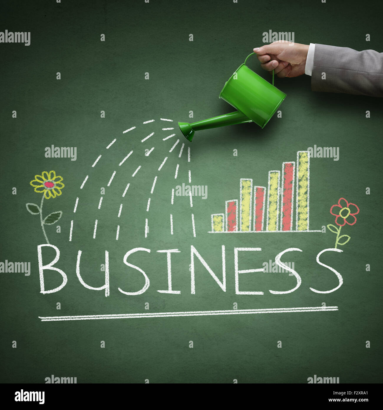 Watering can and word business drawn on a blackboard concept for business growth, investment, savings and making - Stock Image